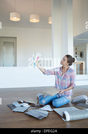 Woman viewing paint swatches in new house - Stock Photo