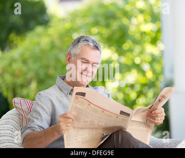 Senior man reading newspaper on patio