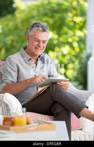 Senior man using digital tablet on patio - Stock Photo