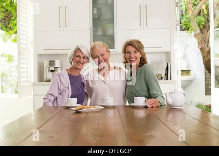 Senior women drinking coffee in kitchen - Stock Photo