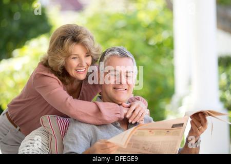 Senior couple reading newspaper on patio - Stock Photo