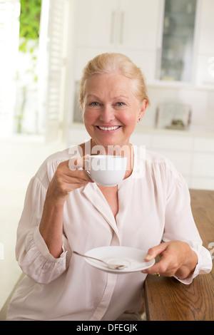 Portrait of senior woman drinking coffee - Stock Photo