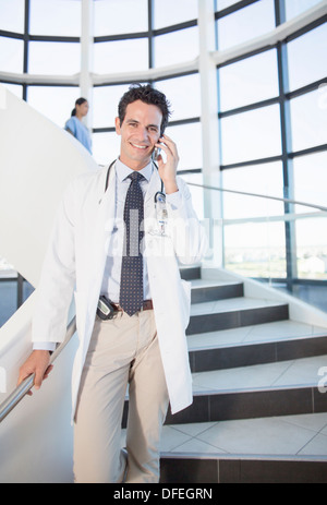 Doctor talking on cell phone in hospital - Stock Photo
