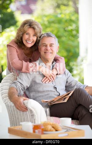 Portrait of smiling senior couple hugging on patio - Stock Photo