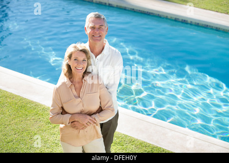Portrait of smiling senior couple at poolside - Stock Photo