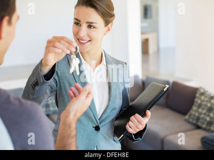 Realtor giving man keys to new house - Stock Photo