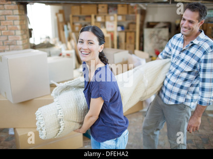 Couple carrying rolled up rug in driveway - Stock Photo