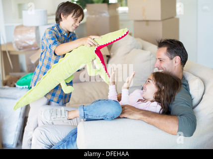 Father and children playing in new house - Stock Photo