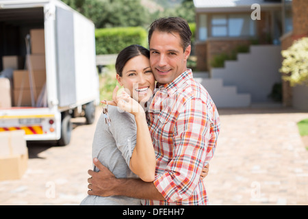 Portrait of smiling couple in front of new house - Stock Photo