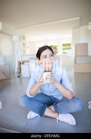 Happy woman enjoying coffee among cardboard boxes - Stock Photo