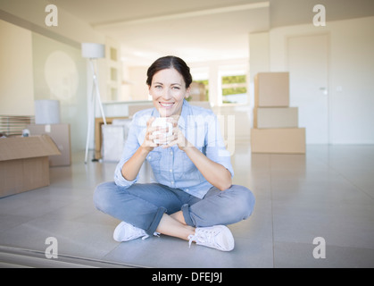 Woman drinking coffee among cardboard boxes - Stock Photo