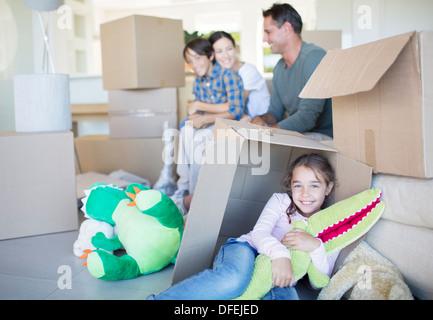 Family among cardboard boxes in livingroom - Stock Photo