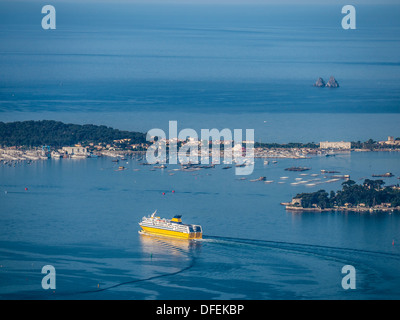 Ferry leaves the harbour of Toulon to Corsica with the Isthme of Sablettes in la Seyne Sur Mer as background - Stock Photo