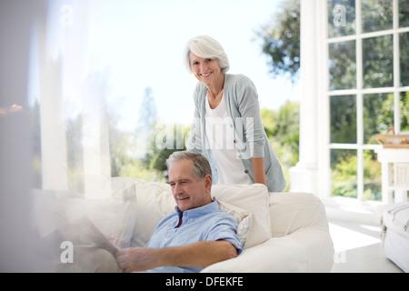 Senior couple relaxing on patio sofa - Stock Photo