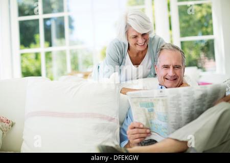Senior couple reading newspaper on sofa - Stock Photo