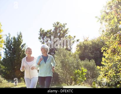 Senior women jogging in park - Stock Photo