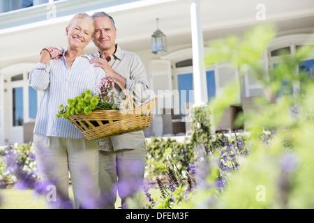 Portrait of senior couple hugging in garden - Stock Photo
