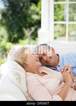 Senior couple laying on patio sofa and holding hands - Stock Photo