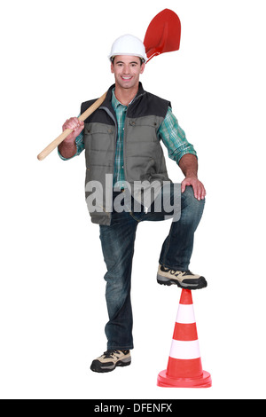 road worker holding a shovel and leaning his foot on a traffic cone - Stock Photo