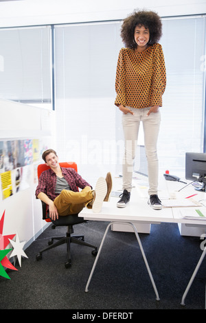 Business woman standing on table in office - Stock Photo