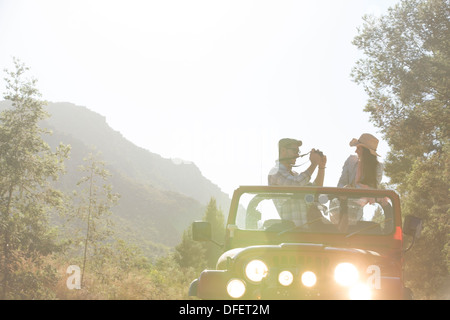 Man taking pictures of girlfriend in sport utility vehicle - Stock Photo