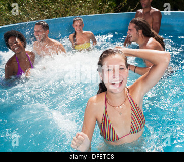 Friends playing in swimming pool - Stock Photo