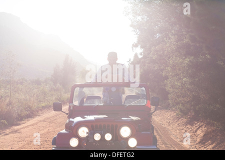 Man standing in sport utility vehicle on dirt road - Stock Photo