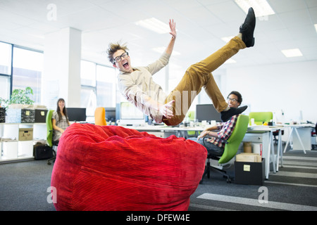 Businessman jumping into beanbag chair in office - Stock Photo