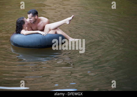 Couple playing in inner tube in river - Stock Photo