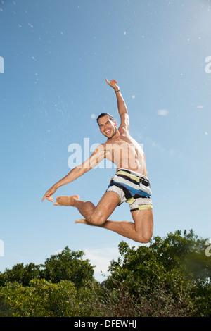 Man in swim trunks jumping - Stock Photo