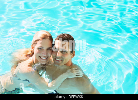 Portrait of smiling couple in swimming pool - Stock Photo
