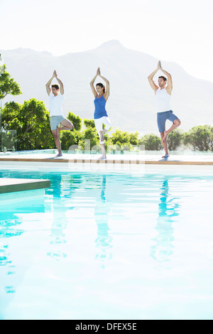 Men and woman practicing yoga at poolside - Stock Photo