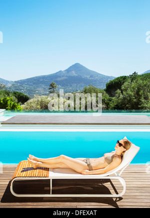 Woman relaxing on lounge chair at poolside - Stock Photo