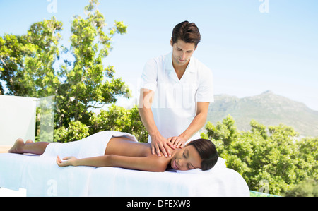 Woman receiving massage on patio at spa - Stock Photo