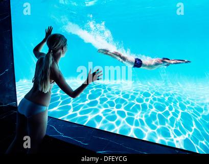 Woman watching boyfriend underwater in swimming pool - Stock Photo