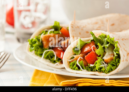 Breaded Chicken in a Tortilla Wrap with Lettuce and Tomato - Stock Photo