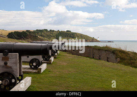 Cannons of St Mawes Castle with St Anthony Head lighthouse in the distance, Cornwall - Stock Photo