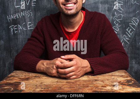 Happy young man is sitting in front of blackboard with positive words written on it - Stock Photo