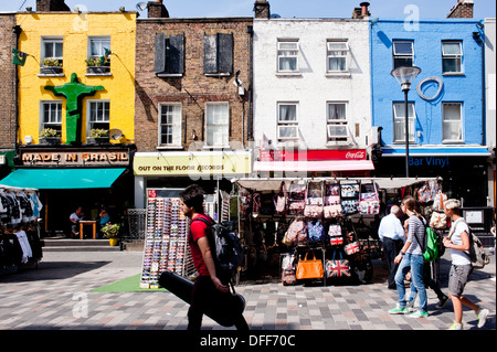 Tourists and locals walk past stalls and shops in Inverness St in Camden, London on August 21, 2013. - Stock Photo