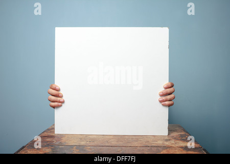 Young man sitting at a table and holding a blank white sign, only his fingers are visible - Stock Photo