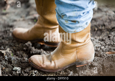 close up, cowboy boots in mud - Stock Photo