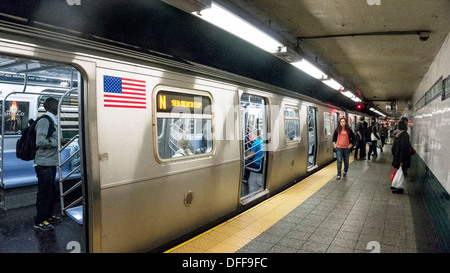diverse passengers on platform & inside train as N line train makes stop at Manhattan Chinatown Canal street subway - Stock Photo