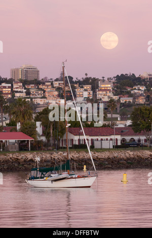 Full moon rising at sunset over harbor, San Diego, CA. - Stock Photo