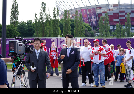 Japanese film team with Polish football fans in front of the National Stadium in Warsaw Poland during the EURO 2012 - Stock Photo