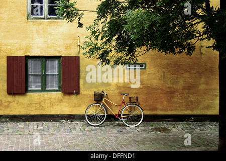 Yellow façade of building in Copenhagen with bicycle propped up against it. Leafy tree on right side of frame. Denmark. - Stock Photo