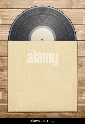 Old vinyl record in a paper case, on wooden table. - Stock Photo
