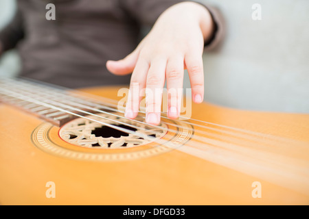 Young girl, 4 years old, playing on an acoustic guitar. - Stock Photo
