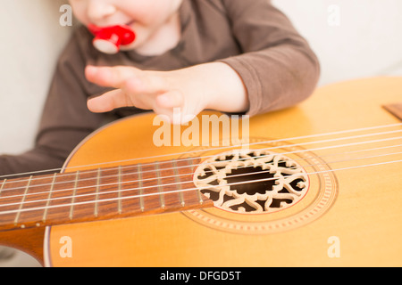 Young girl, 4 years old, playing with an acoustic guitar. - Stock Photo