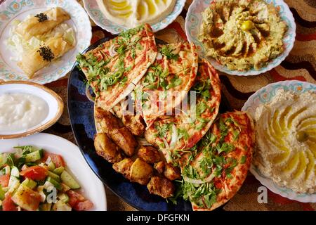 Food: different ´meze´ salads, ´hummus´ and more, with chiken ´kebab´ grill and bread, ´pizza´ style, Hama, Syria - Stock Photo