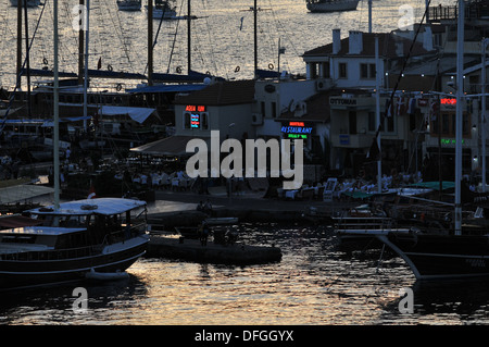 Lights begin to come on as evening falls over the old quayside of Marmaris, Turkey, on a late summer evening - Stock Photo